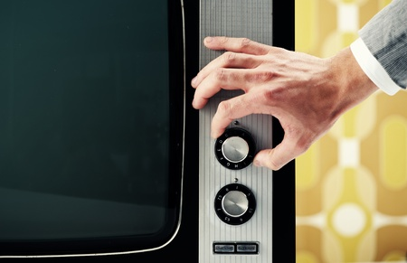 turn the dial: Man  turning channel knob on retro television