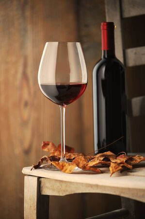 merlot:  glass of red wine on a wooden chair, with dry leaves and a bottle of red wine on background