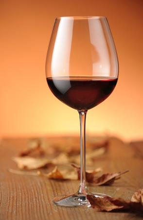 hojas secas: vaso de vino tinto en un estante de madera, con hojas secas