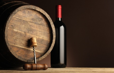 red wine bottle, wodden barrel and corkscrew  photo