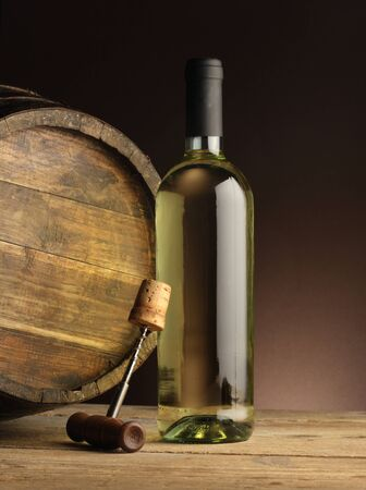 white wine bottle, woodden barrel, and corkscrew  photo
