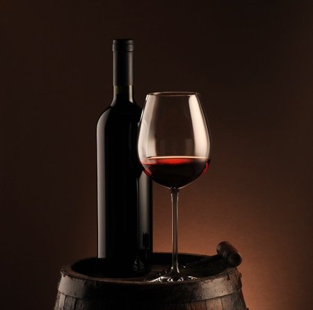 wine cellar: red wine bottle and wine glass on wodden barrel