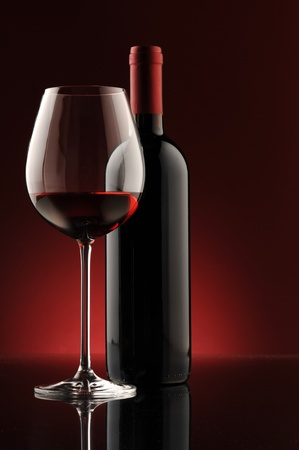 red wine bottle and wine glass , red light on background photo