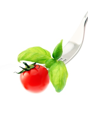 tomato on a fork,isolated on white background photo