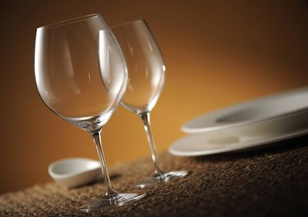 dof: Dinner place setting with plates, glasses and cutlery shallow dof  Stock Photo