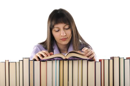 young woman reading a book behind a big pile of books  photo
