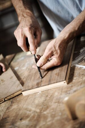 wood craft: hands of the craftsman carve a bas-relief with a gouge
