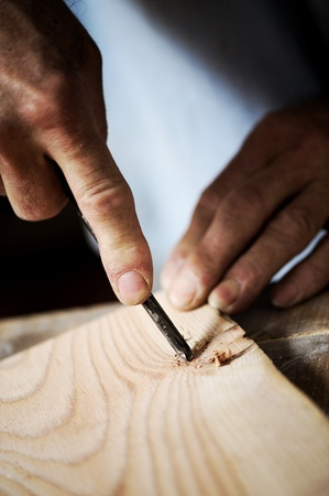 professionalism: hands of the craftsman carve a bas-relief with a gouge