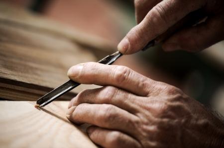 Hände der Handwerker schnitzen ein Flachrelief mit dem Stichel Standard-Bild