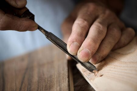 craftsmen: hands of the craftsman carve a bas-relief with a gouge