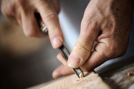 falegname: mani dell'artigiano scolpire un bassorilievo con una sgorbia Archivio Fotografico