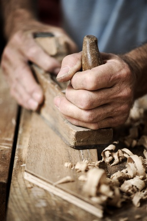 hands of a carpenter planing a plank of wood with a hand plane photo