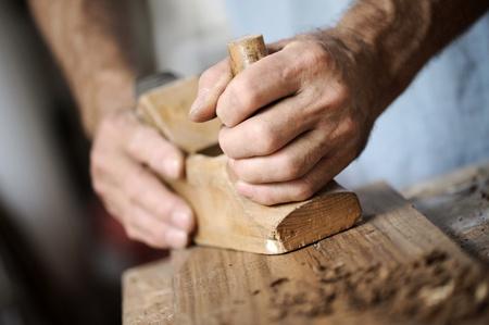 carpintero: manos de un carpintero cepillar una tabla de madera con un cepillo de mano