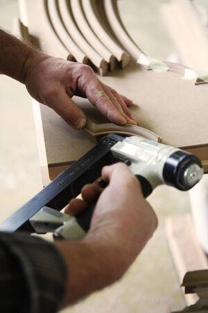 grapadora: manos de un carpintero utilizando una pistola de aire atacante