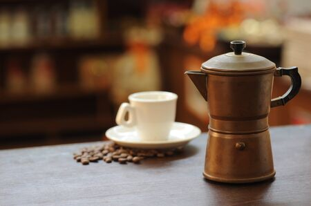 with coffee maker: old coffee maker on wooden table, coffee cup on background