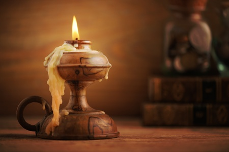 old candle on a wooden table, old books in the background photo