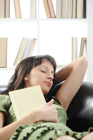 young woman is sleeping on a sofa in the living room with a book , bookshelf on background Stock Photo - 12079016