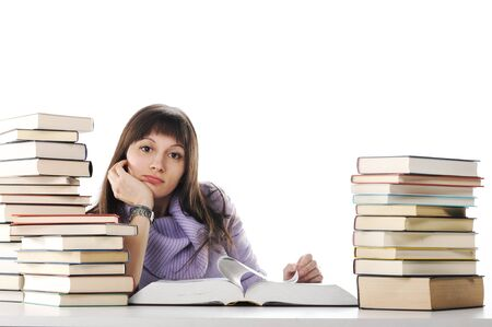 Tired of studies, A beautiful young woman sitting at a desk with two large piles of books. photo