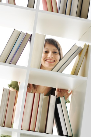 book shelf: young Woman looking for a book at the library