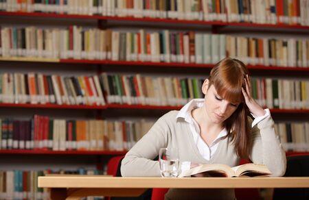 mujer leyendo libro: Retrato de un estudiante serio joven que lee un libro en una biblioteca