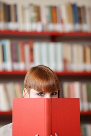 choose university: Girl hiding behind the book,  library on background