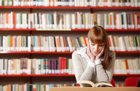 choose university: Portrait of a serious young student reading a book in a library  Stock Photo