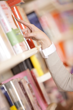 reaching: young woman looking for a book in a bookstore - hand close up