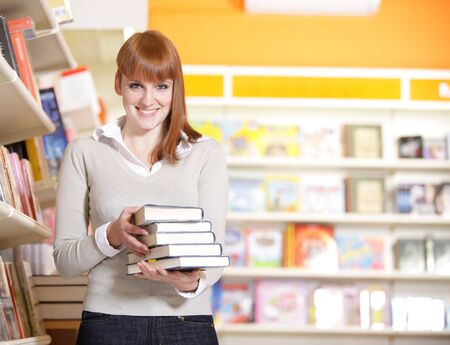 choose university: A portrait of a college student holding books in the library