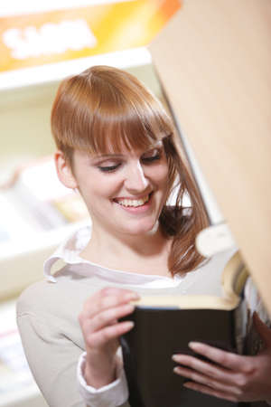 portrait of a young  smiling student in a library  photo