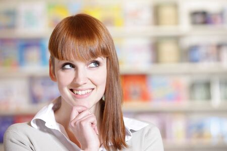 portrait of a  smiling young woman in a library  photo