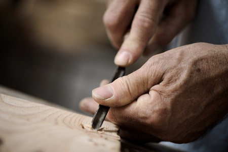 carving tool: hands of the craftsman carve a bas-relief with a gouge