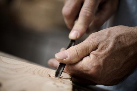 carpintero: manos del artesano tallar un bajorrelieve con una gubia Foto de archivo