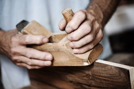 artesano: manos de un carpintero cepillar una tabla de madera con un cepillo de mano