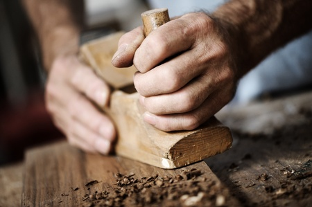 Wood work: hands of a carpenter planing a plank of wood with a hand plane