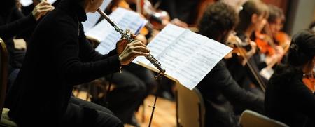 orquesta: Mujer tocando la flauta durante un concierto de m�sica cl�sica Foto de archivo