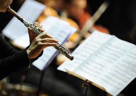 orquesta clasica: Mujer tocando la flauta durante un concierto de música clásica Foto de archivo