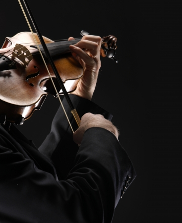 solo violinist: the violinist: Musician playing violin on dark background