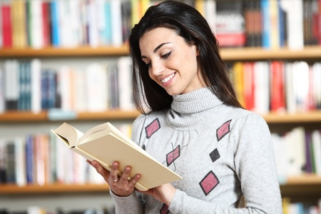smiling female student with book in hands in a bookstore Stock Photo - 12274393