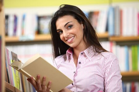 smiling female student with book in hands in a bookstore - model looking at camera.  Stock Photo - 12275116