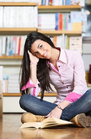smiling female college student sitting on floor in library, reading book Stock Photo - 12274391