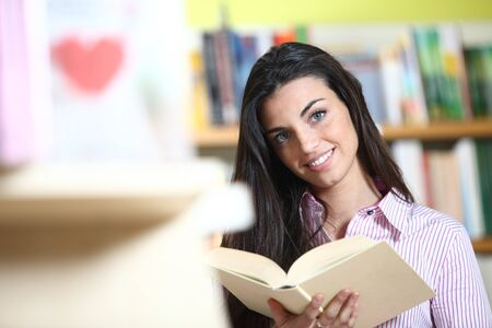 smiling female student with book in hands in a bookstore - model looking at camera.  Stock Photo - 12274037