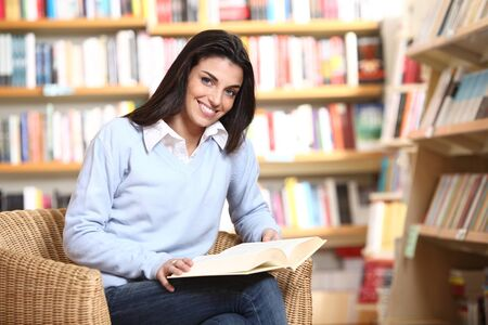 smiling female student with book in hands sitting in a chair in a bookstore - model looking at camera.  photo