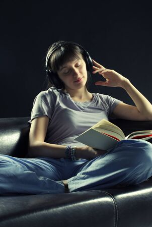Relaxed young woman listening music and reading a book photo