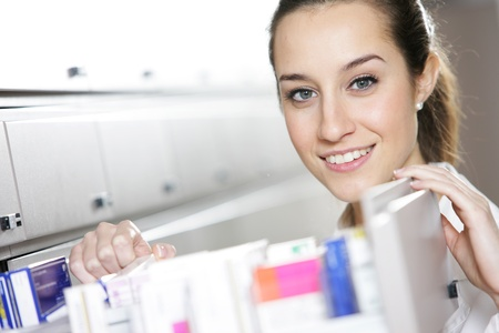 pharmacist: Young female pharmacist reaching for medicine  Stock Photo