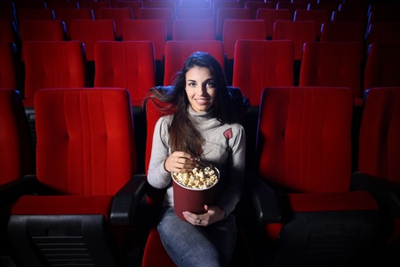 portrait of a pretty young woman sitting in an empty theater, she eats popcorn and smiles, front view photo