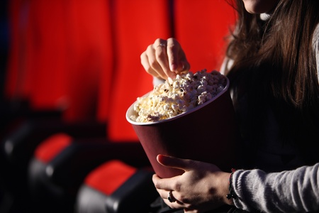 spectators: close up of the hands of a girl in a movie theater, she eats popcorn