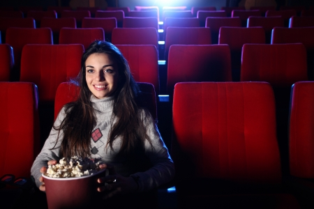 a pretty girl alone sitting in a empty movie theater, she eats popcorn and smiles photo