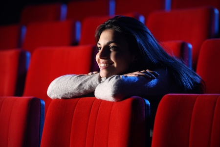experiences: funny movie: portrait of a pretty girl in a movie theater, she leans her elbows on the back row of chairs in front of her, totally relaxed