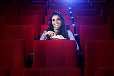 portrait of a pretty young woman, she sitting in an empty theater, eats popcorn and smiles photo