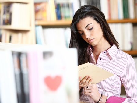 bookstore: female student reading a book in library